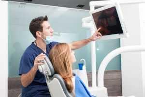 A dentist showing her teeth through a screen