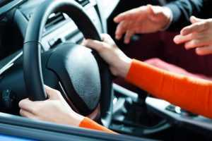 A young person being given driving tips by someone else