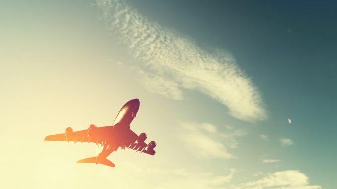 Airplane taking off at sunset