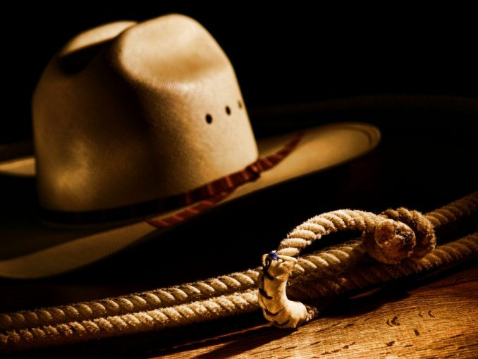 American West rodeo cowboy lasso rope and white straw hat