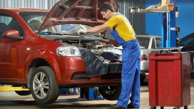 young mechanic doing car maintenance