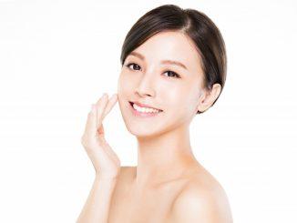 Asian woman applying cream