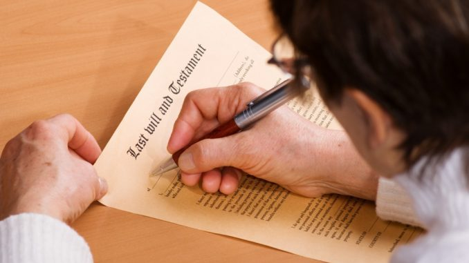 A man signing on his last will document