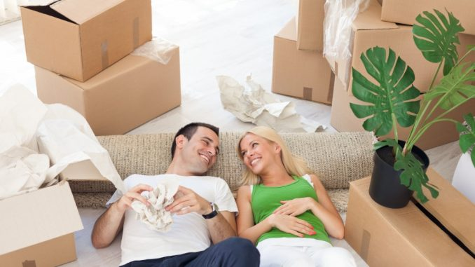 Young smiling couple relaxing in the middle of cardboard boxes in new home
