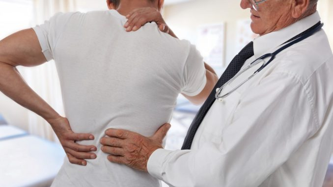 doctor diagnosing man's back