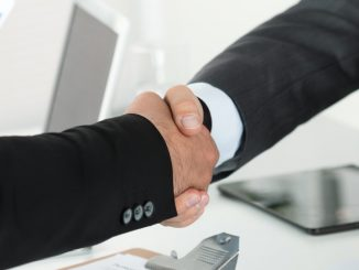 two businessman shaking hands with each other in the office after business sale