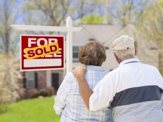 an old couple standing in front of a house they just bought