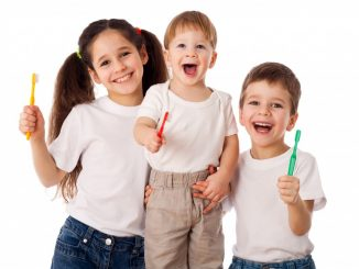 Kids smiling while holding a toothbrush