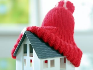 a miniature house with a snow hat