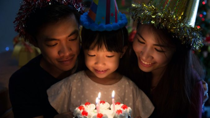 Birthday girl about to blow candles with parents