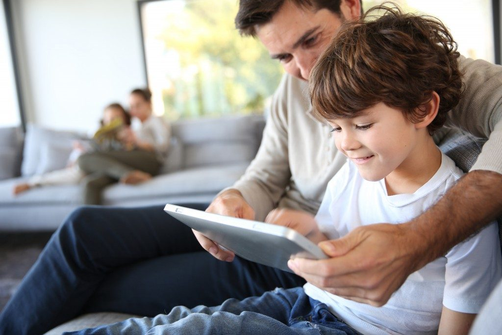 Father and son playing tablet