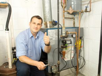 Plumber posing beside a gas furnace