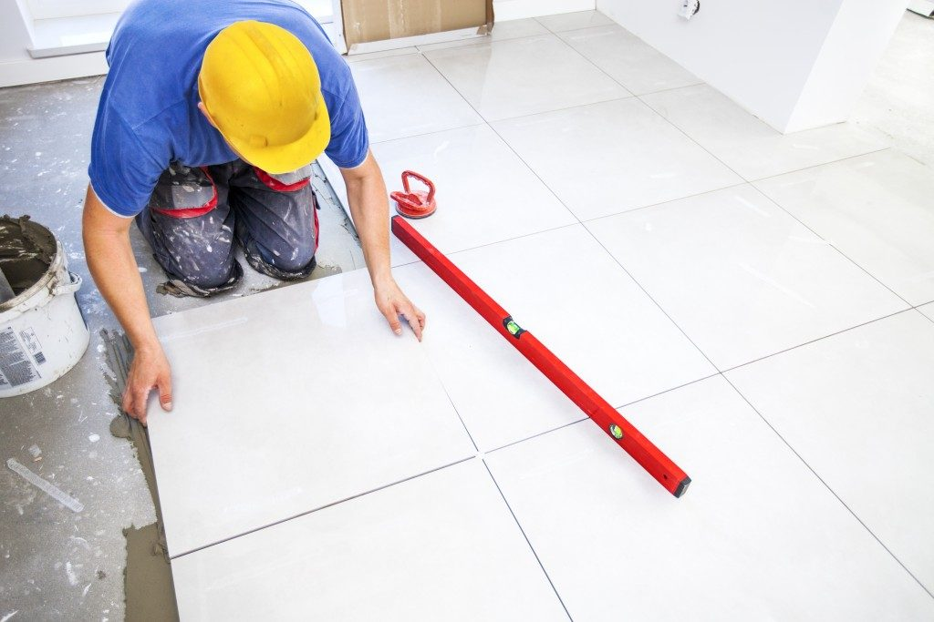 worker attaching bathroom tiles