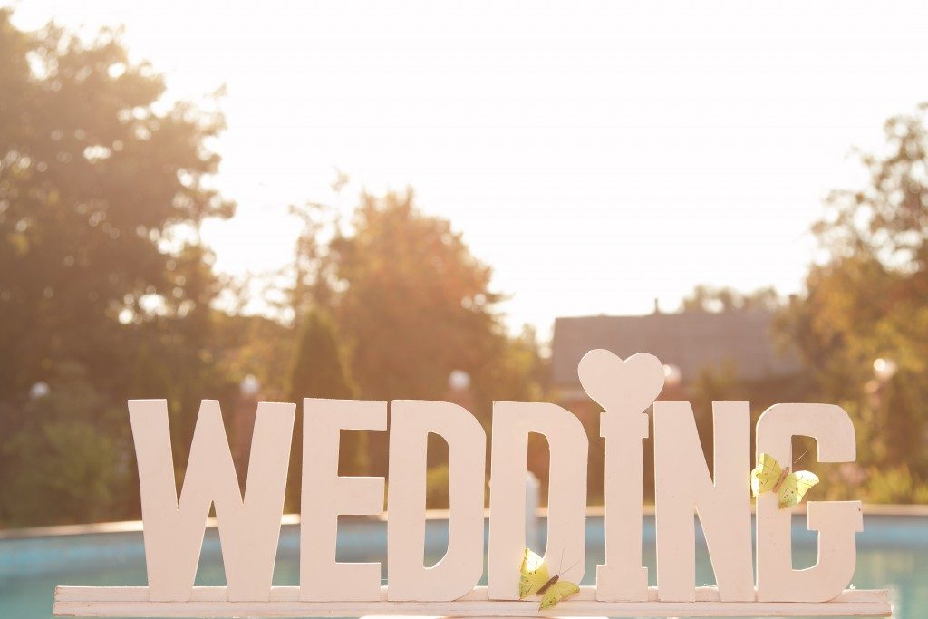 Word wedding, white letters on a board with a pool of blue water