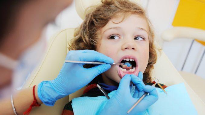 kid having his teeth checked by dentist