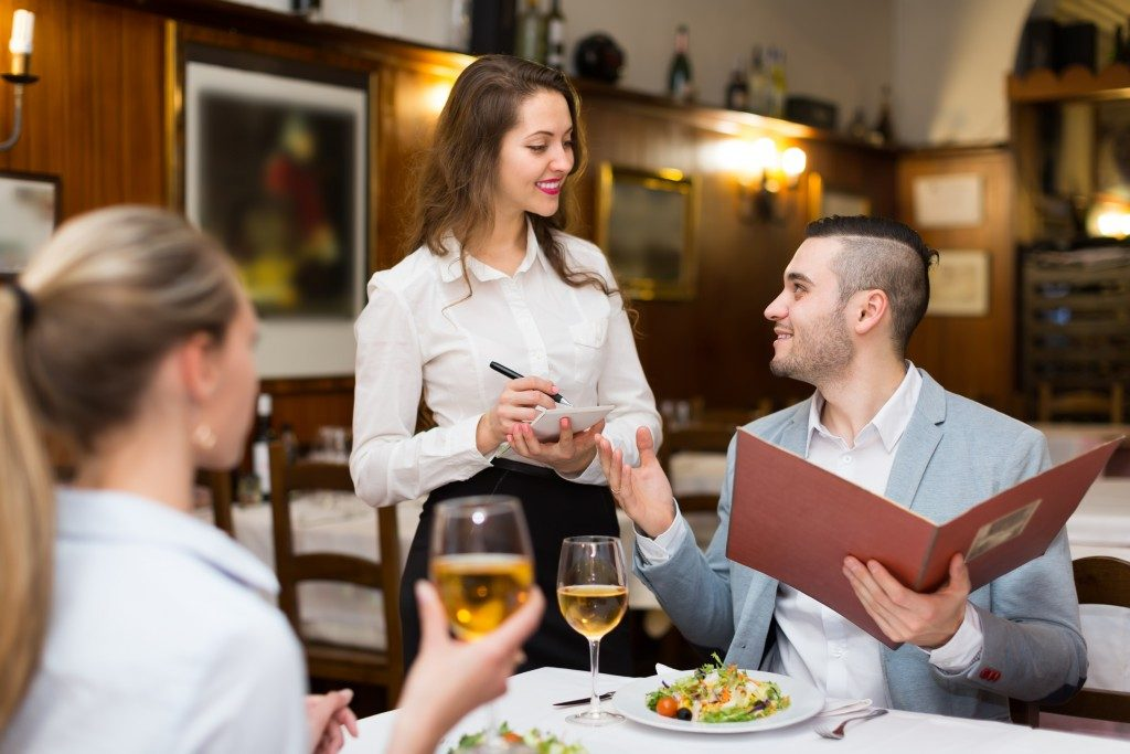 waitress offering tasty dishes to guests couple