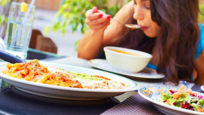 woman eating in an outdoor restaurant