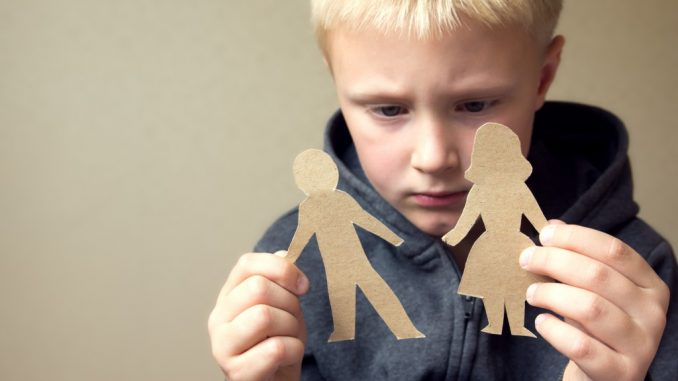 Child holding a cut out of a man and woman representing his parents