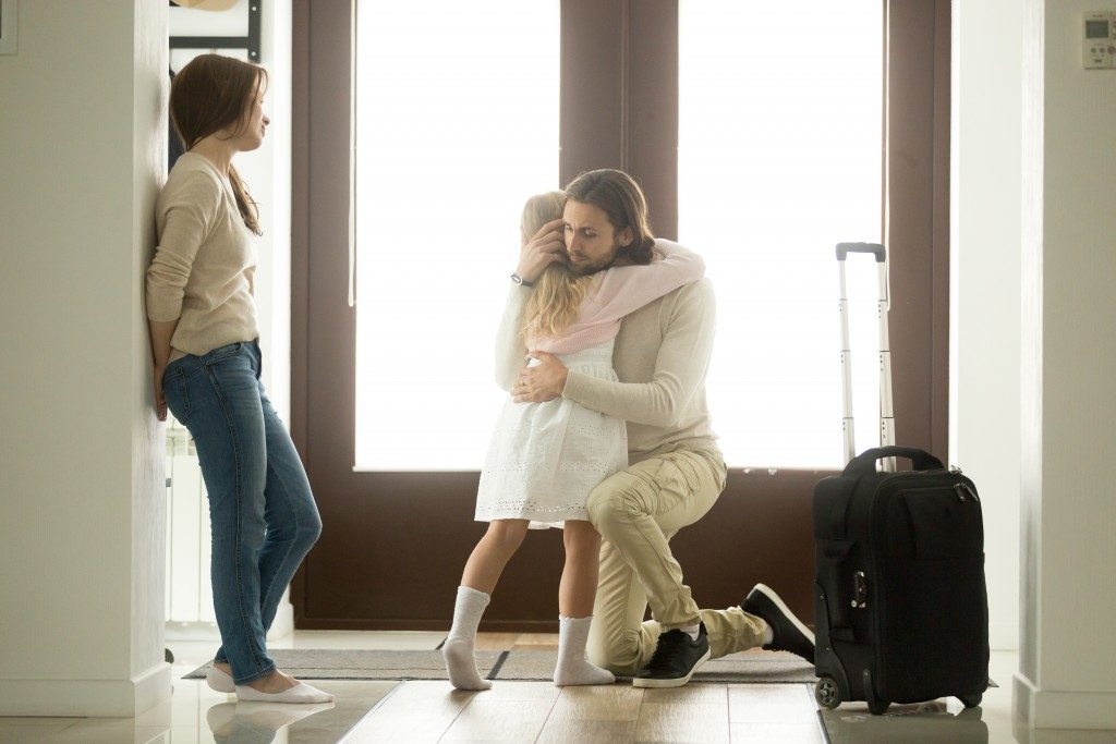 Littile girl hugging her father before he leaves