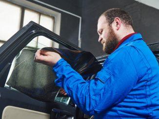 man installing tint on car