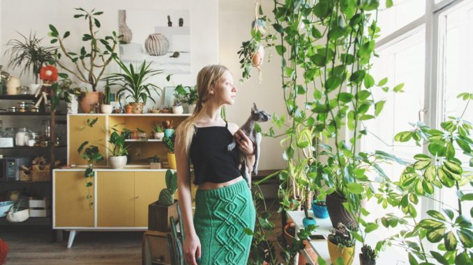 girl standing surrounded by plants