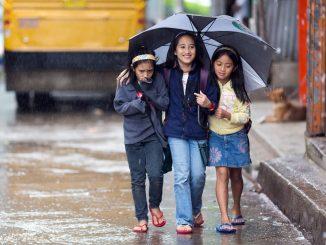 kids sharing an umbrella