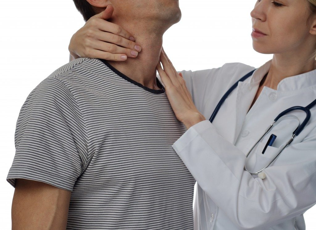doctor massaging patient's throat