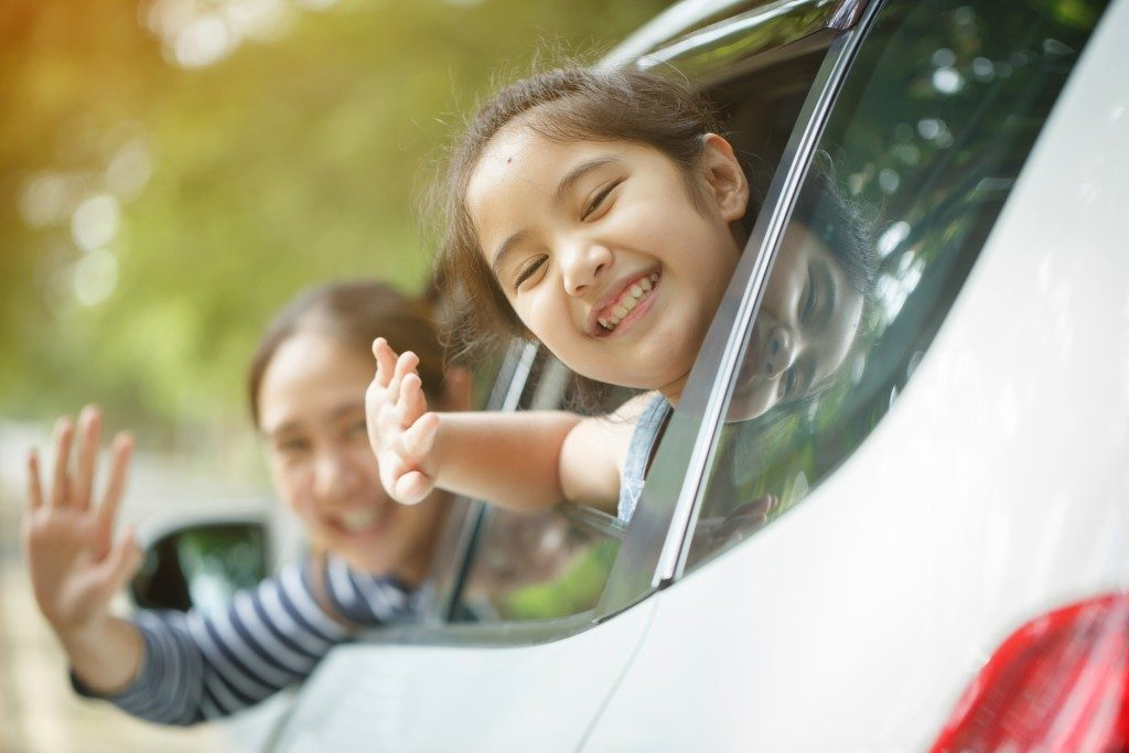 child and mother waving in the car