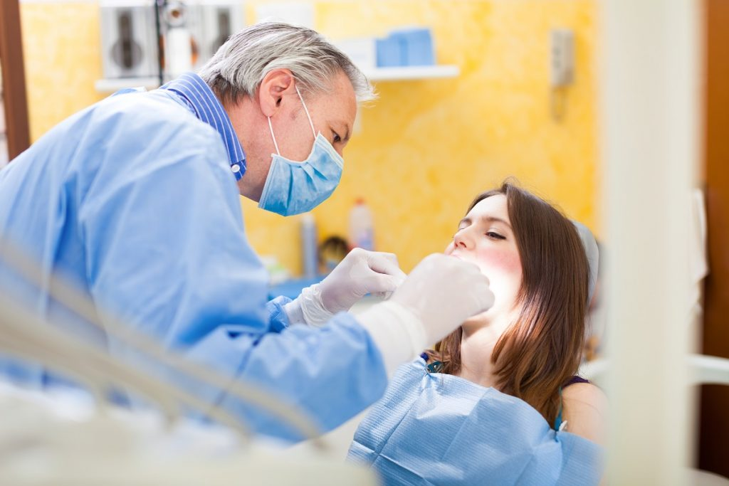 senior dentist foused while treating his patient