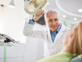 senior dentist adjusting the light before the treatment his patient