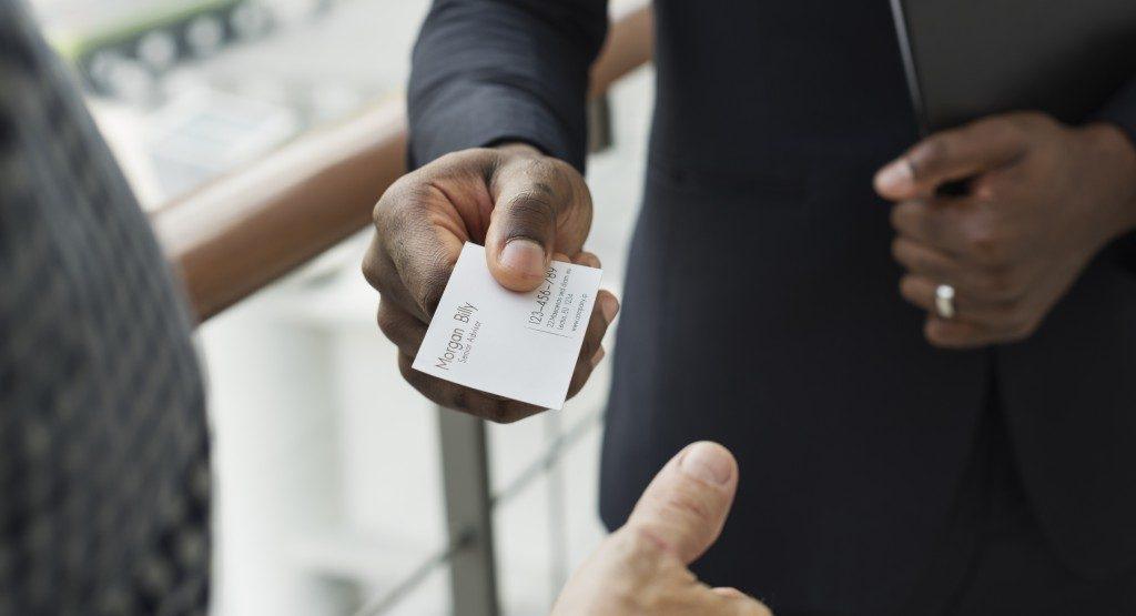 Business man handing over a business card