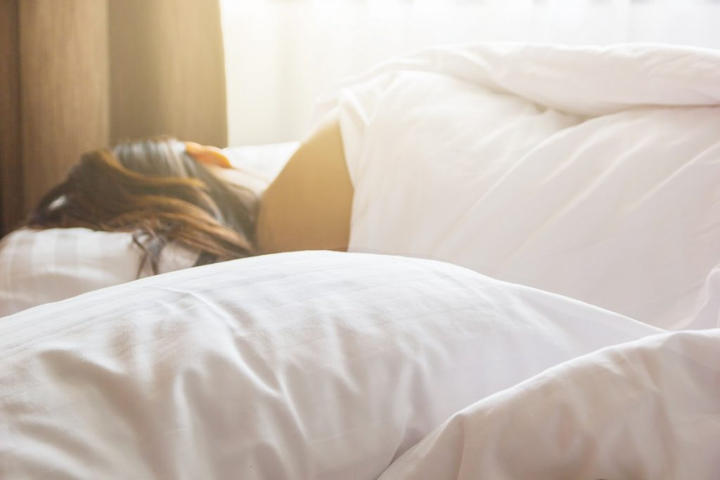 back of a woman sleeping in bed