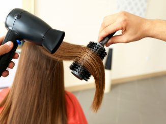 straightening woman's hair in a salon