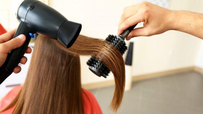 straightening woman's hair in a salon