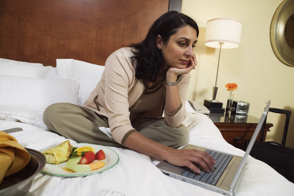 woman sitting on hotel bed while working and eating