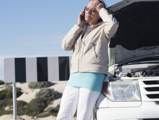woman on the phone on the side of ride broken down car